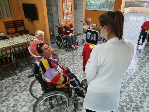 Finalista do MasterChef Brasil, Lorane Dayse, em tela de robô conversando com idosa sentada em cadeira