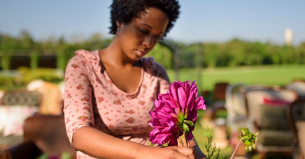 Mulher negra arrumando flores