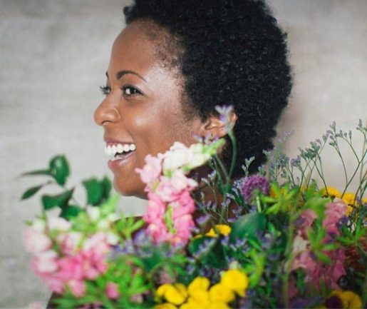 Mulher negra sorrindo por trás de flores