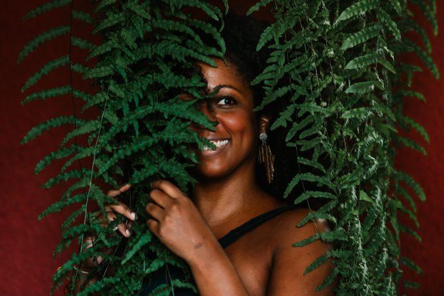 Mulher negra atrás de plantas