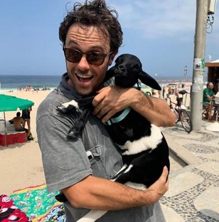 Ator Kayky Brito segurando ovelha na praia