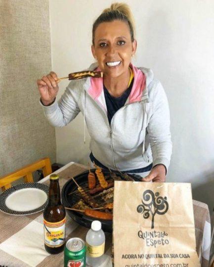 Rita Cadillac comendo um espeto de carne com cerveja e uma frigideira de petiscos à mesa
