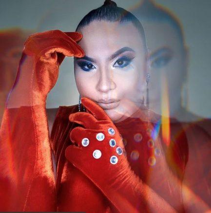 Mulher trans com vestido vermelho, rosto maquiado e cabelo montado