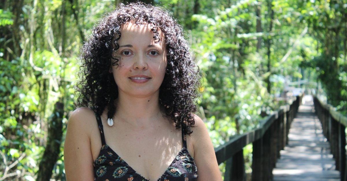Mulher de cabelos cacheados em ponte dentro da floresta da Amazônia