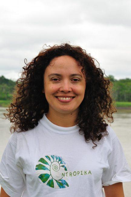 Mulher de cabelos cacheados e camisa branca sorrindo à frente de um rio