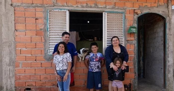 família em frente de casa inacabada