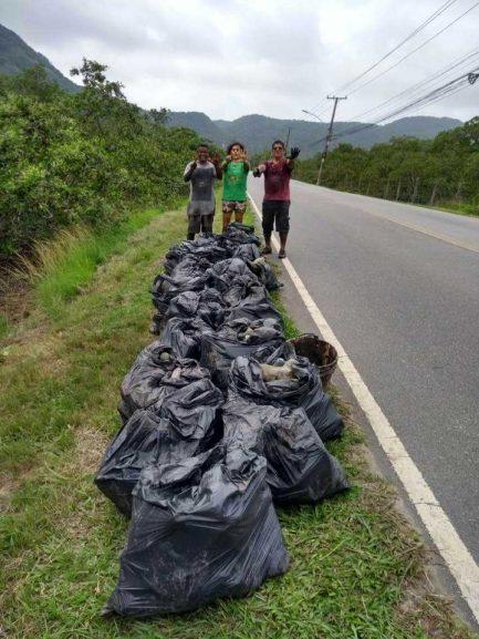 Pessoas com sacos de lixo à margem de rodovia