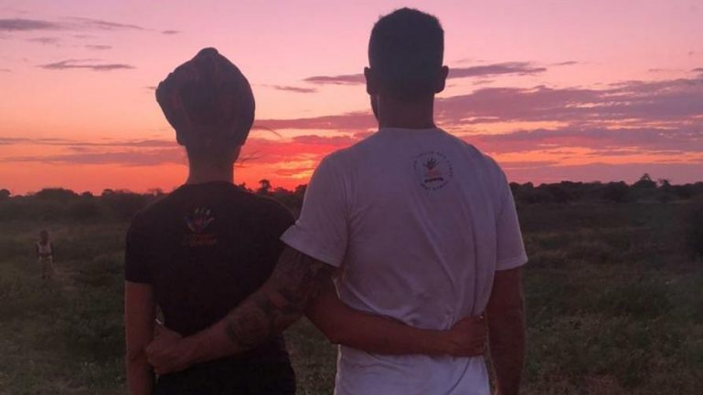 Homem e mulher abraçados de costas vendo o por do sol