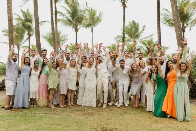 Convidados e noive juntos com as mãos para cima em casamento