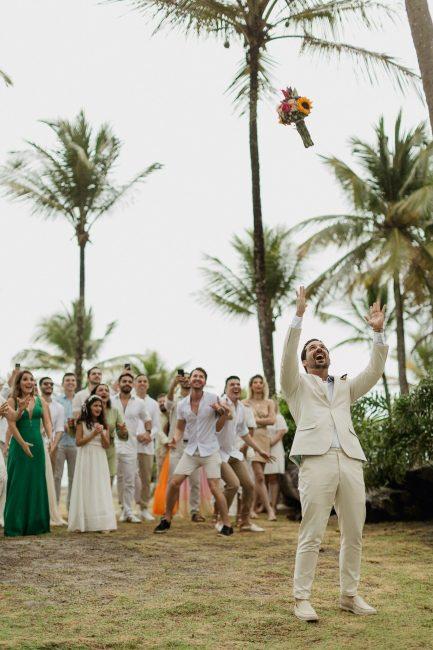 Noivo jogando buquê em festa de casamento solo