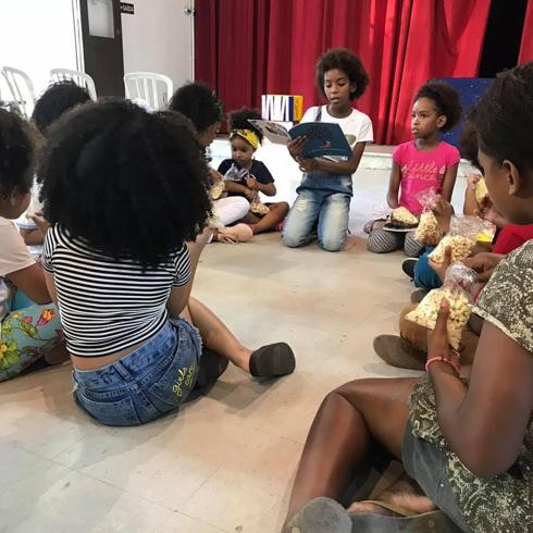 meninas negras sentadas chão roda leitura