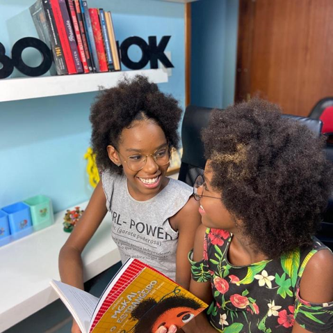 meninas negras sorrindo segurando livro