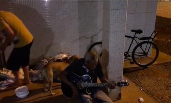 Homem em situação de rua tocando violão na calçada