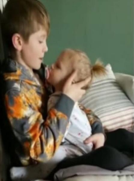 irmão tranquiliza irmã no colo
