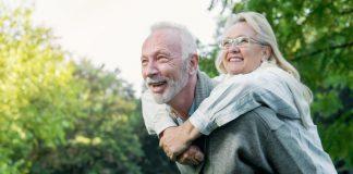 Idosa abraçada nas costas de idoso