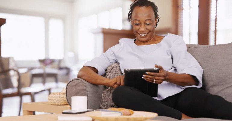 Idosa negra sentada em sofá com tablet nas mãos
