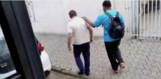 Cego se apoiando em ombro de motorista de ônibus para caminhar pela rua