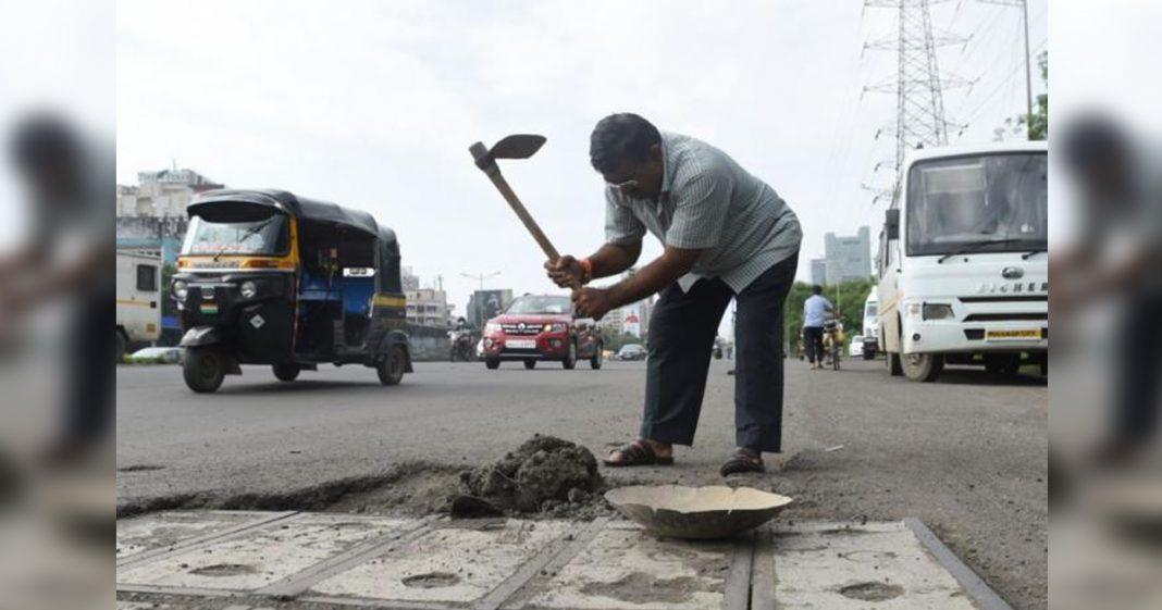 homem conserta buraco rua índia