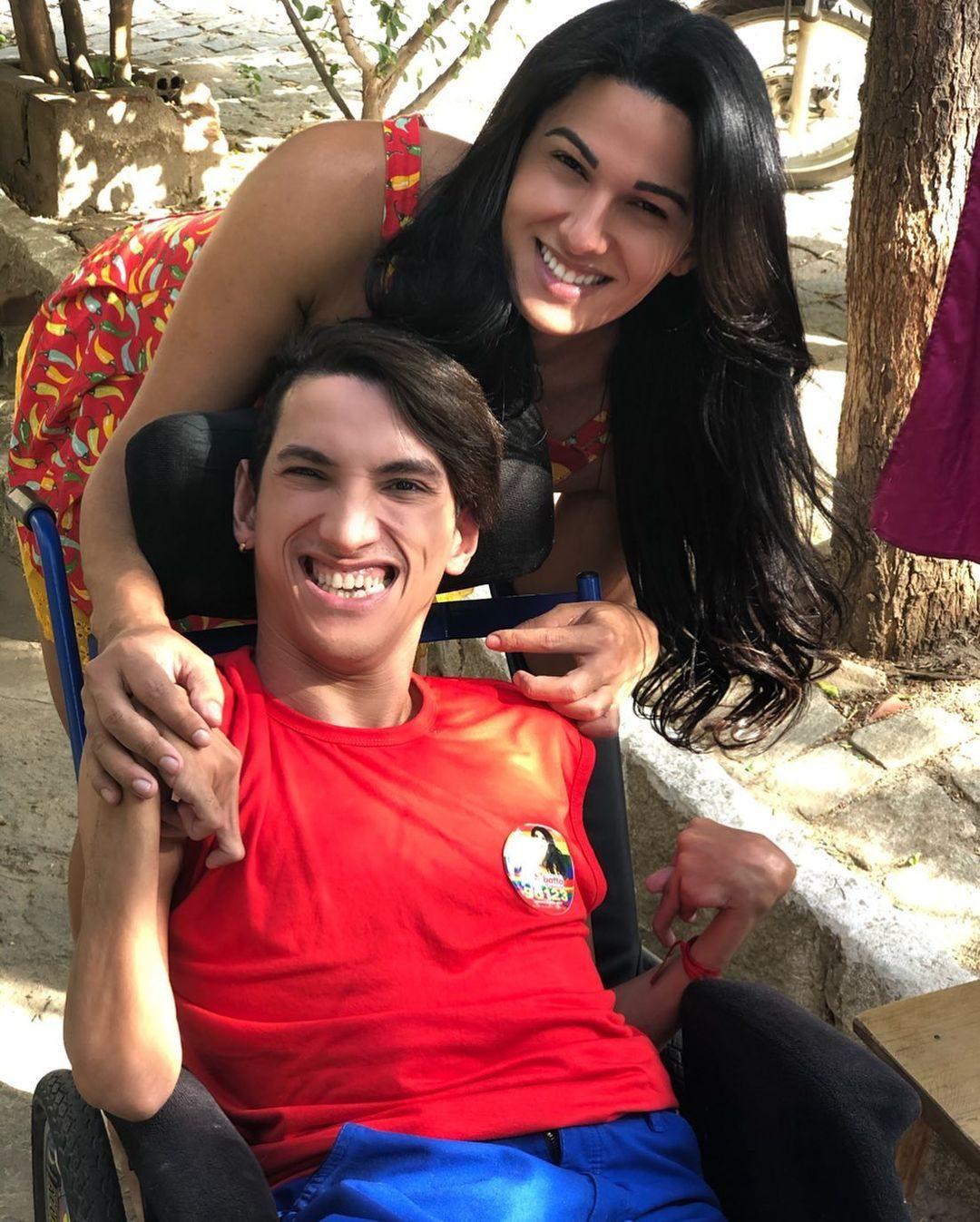 mulher trás cadeira rodas irmão sorrindo