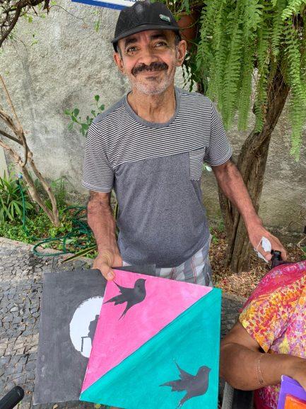 Idoso sorrindo e segurando tela com pintura de pássaros