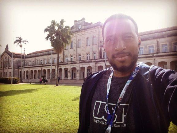Jovem com camisa da USP na universidade