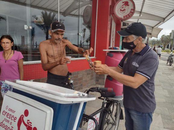 Homem em bicicleta entregando bolachas a pessoa em situação de rua