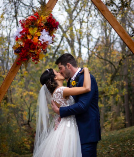 Noivo e noiva se beijando em jardim arborizado