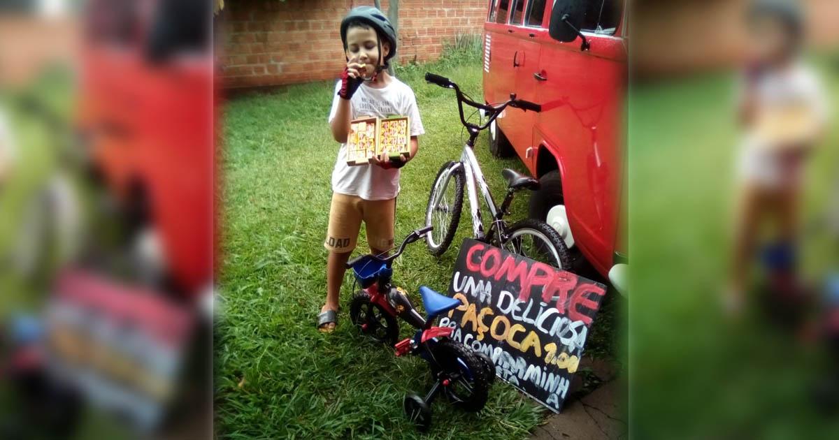 menino segurando caixa paçoquinhas ao lado bicicleta