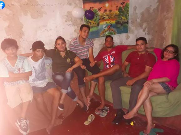 Mãe sentada com seis filhos em sofá na sala de casa