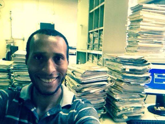 Homem sentado em escritório com vários papéis em volta