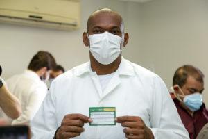 Técnico de enfermagem segurando com cartão de vacinação da covid-19