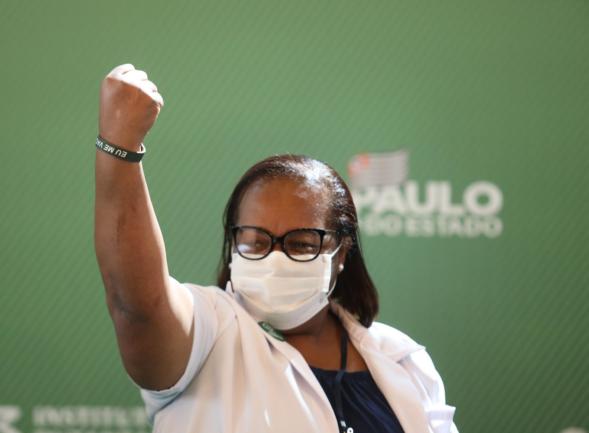 Enfermeira com braço em punho após ter sido vacinada da Covid-19