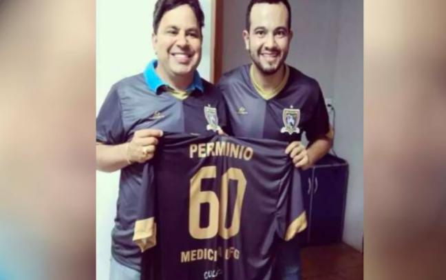 Dois homens sorrindo segurando camisa de time