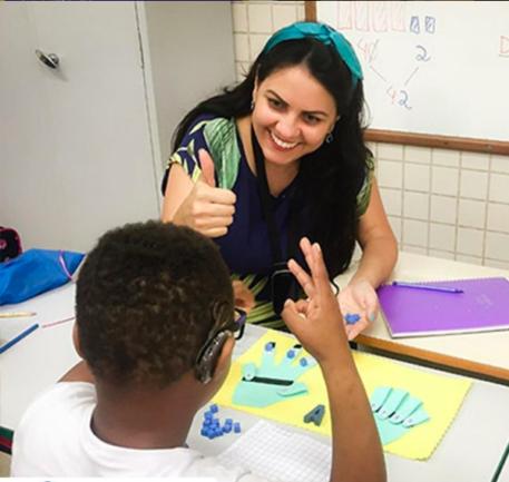 Professora ensinando aluno em Libras
