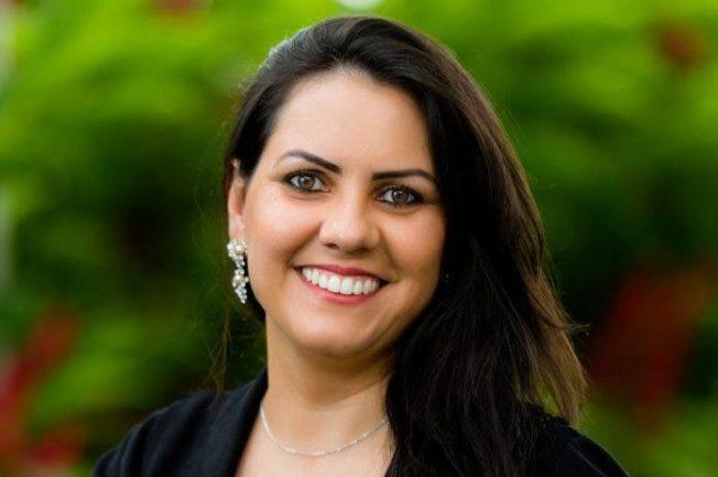 Mulher, professora de Libras, sorrindo com fundo verde