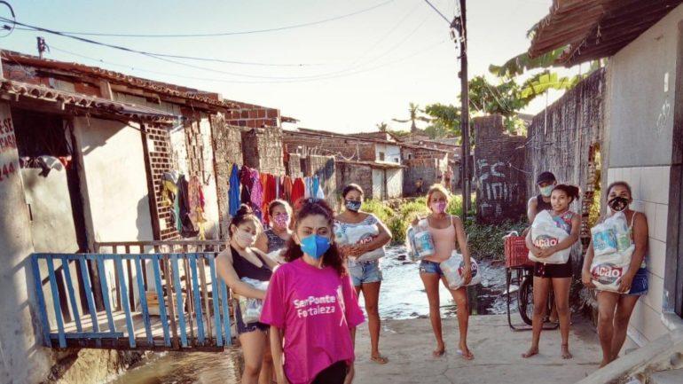 Mulheres em rua com cestas básicas na mão