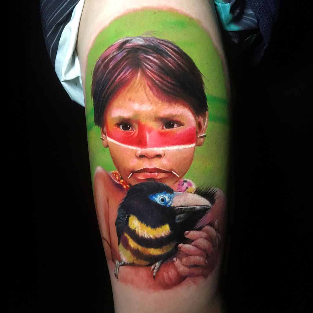 tatuagem criança indígena com pássaro nos braços