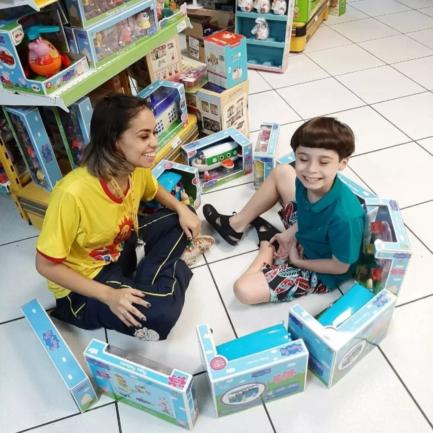 Menino autista sentado com vendedora de loja brincando com brinquedos no chão da loja