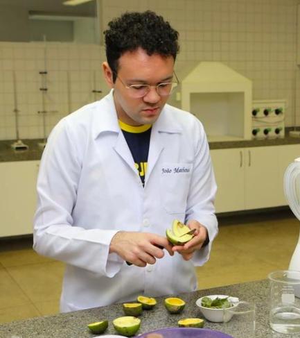 Estudante em laboratório manuseando pequi