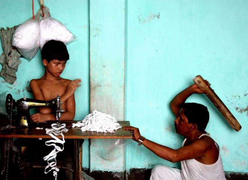 dono fábrica batendo menino trabalhando máquina costura