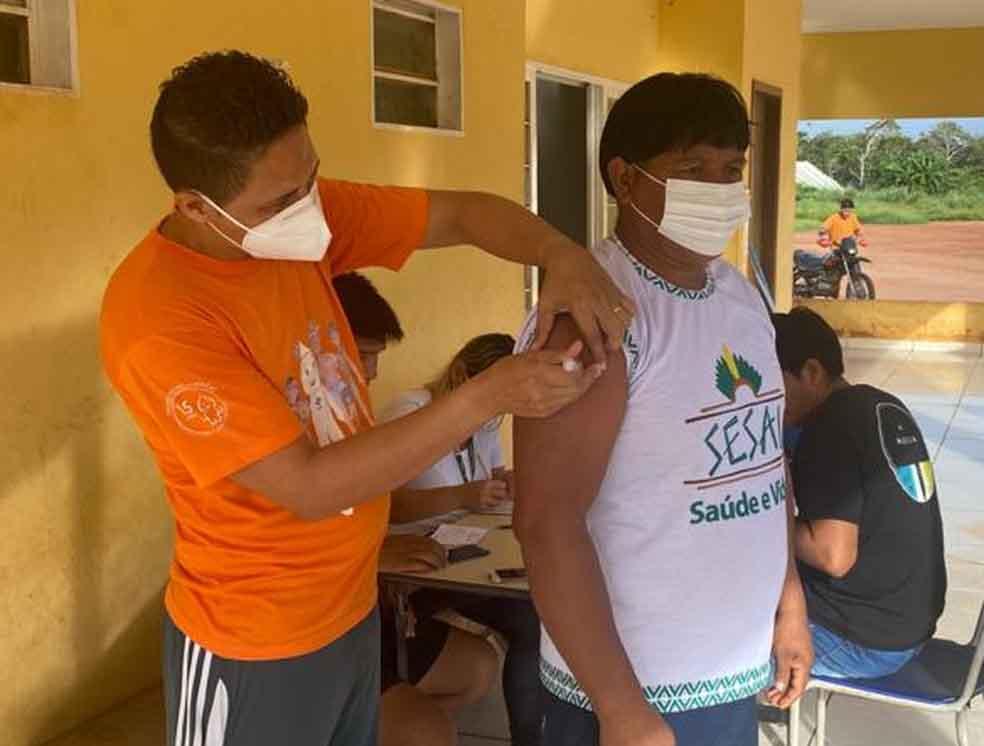 enfermeiro vacinando índio contra coronavírus