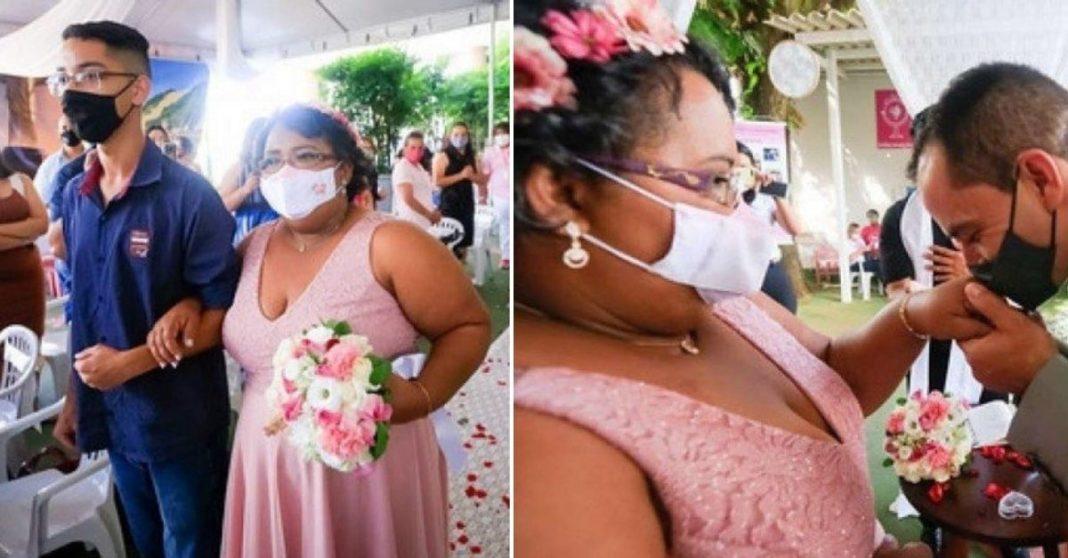 Mulher com câncer entrando com o filho, vestida de rosa, em cerimônia de casamento dentro de hospital e noivo dando beijo na mão da noiva