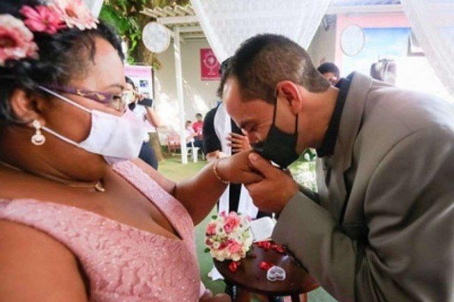 Noivo beijando aliança na mão de noiva
