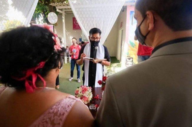 Noivo e noiva de costas para a câmera e de frente para padre em casamento realizado dentro de hospital