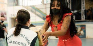 Musa de escola de samba de carnaval de vestido vermelho entregando cesta básica a uma mulher