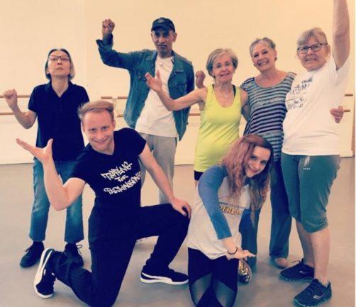Professor e alunos de dança fazendo pose para fotos