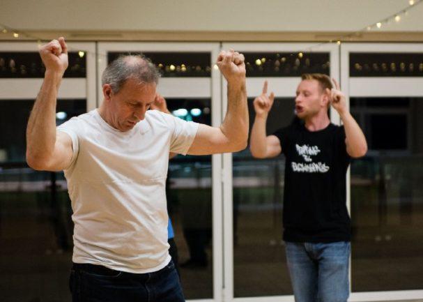 Homem com Parkinson dançando com instruções de professor ao lado