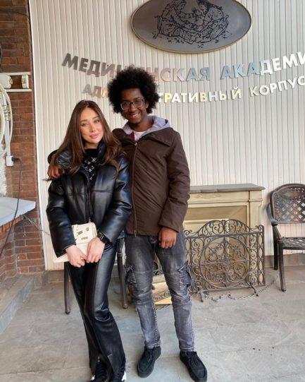 Homem negro com mulher branca abraçados em recepção de faculdade russa de medicina