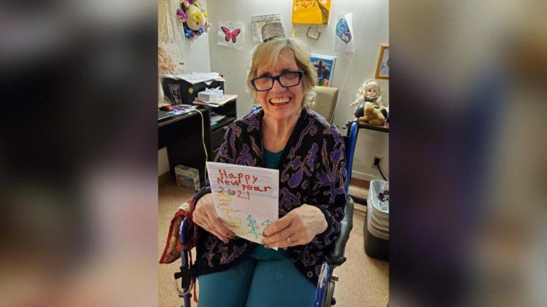 Idosa segurando cartão de ano novo sentada em cadeira de rodas e sorrindo