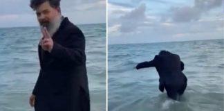 Homem entrando no mar de terno e gravata